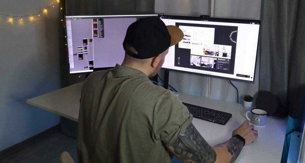 man in green dress shirt and black cap sitting in front of computer