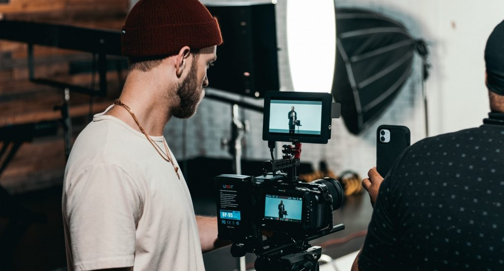 man in white polo shirt standing in front of black video camera
